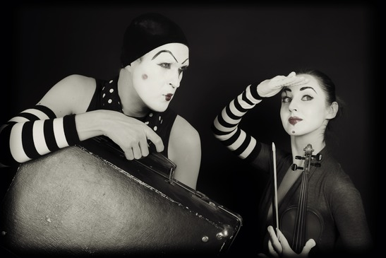 mimes woman and man with suitcase and violin