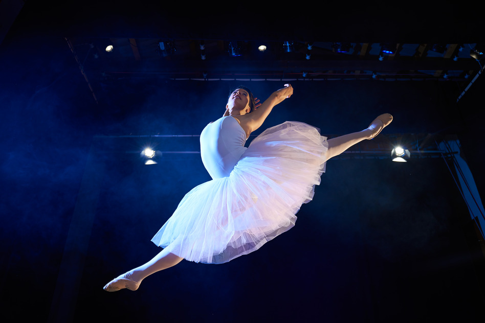 female classic dancer jumping mid air during ballet